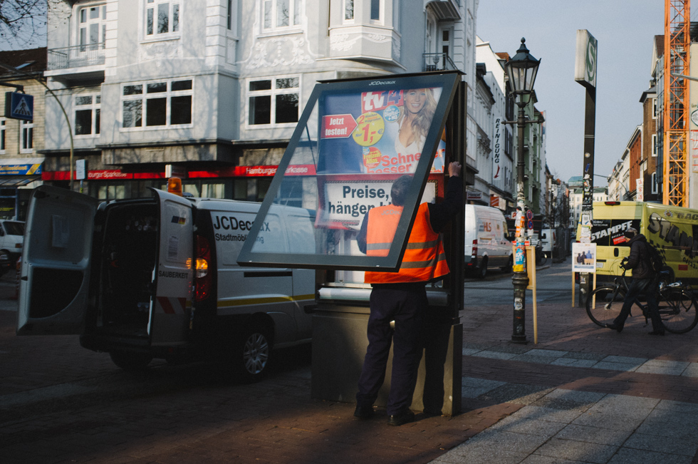 Mann tauscht Plakate in Altona, Hamburg