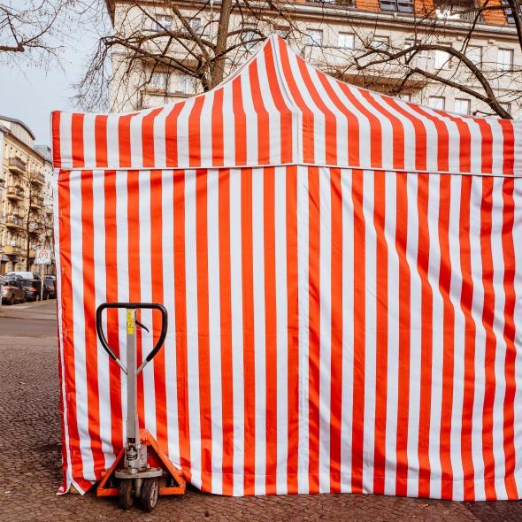 Ein rot-weiß gestreiftes Zelt auf einem Flohmarkt